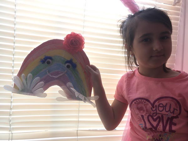 child holds a smiling rainbow near the window