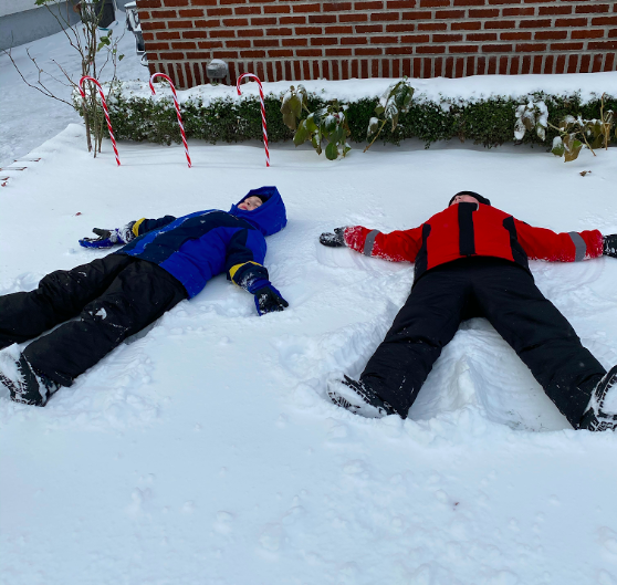 two friends laying the in snow making snow angels