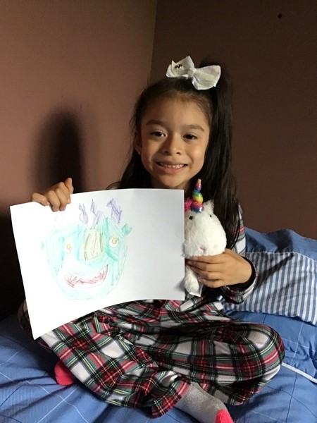 girl holds her picture and stuffed unicorn