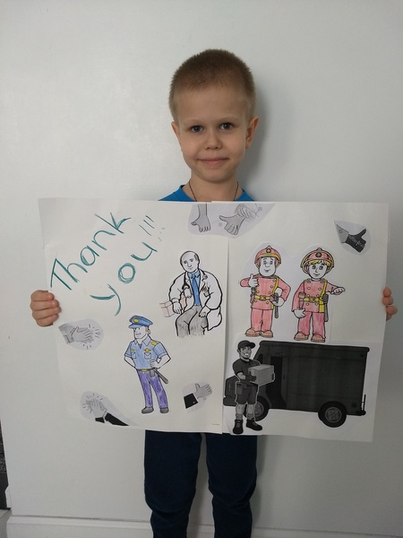 child holds a poster thanking the workers