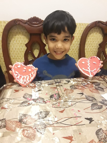 boy in blue shirt showing two decorated cookies