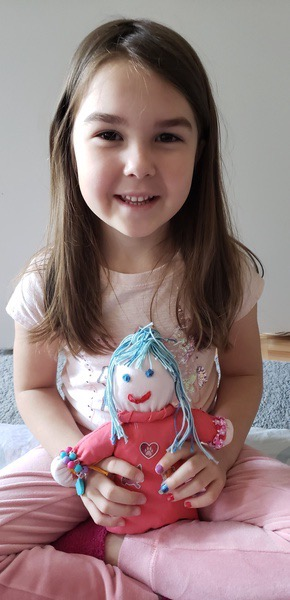 girl holds the doll she made