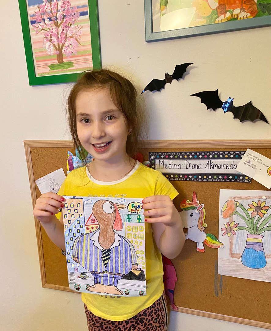 Girl holding turkey with striped shirt