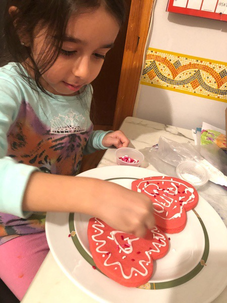 student decorating her two heart shaped cookies
