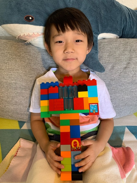 Child shares building made with Legos