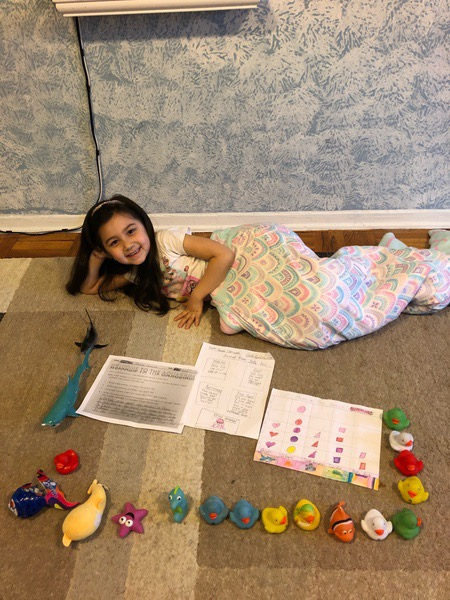 girl laying on floor with lots of papers
