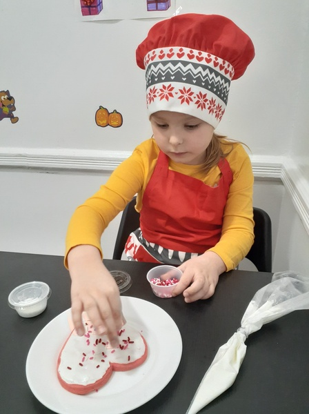 girl in chef's hat decorates her cookies