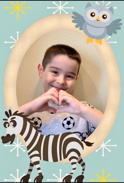 boy makes a heart with his hands