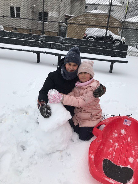 siblings playing in the snow with a snowman