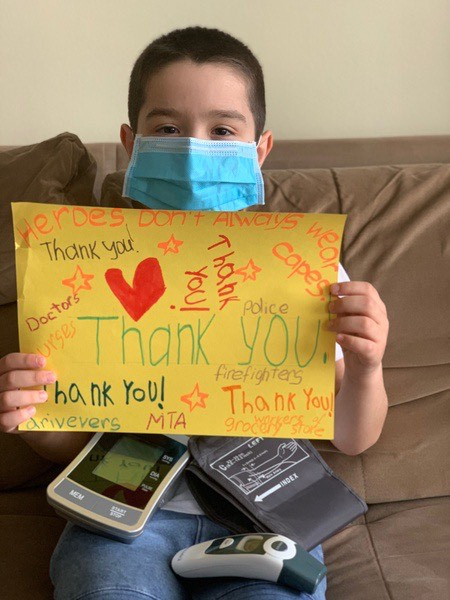 child holds a yellow thank you sign while wearing a mask