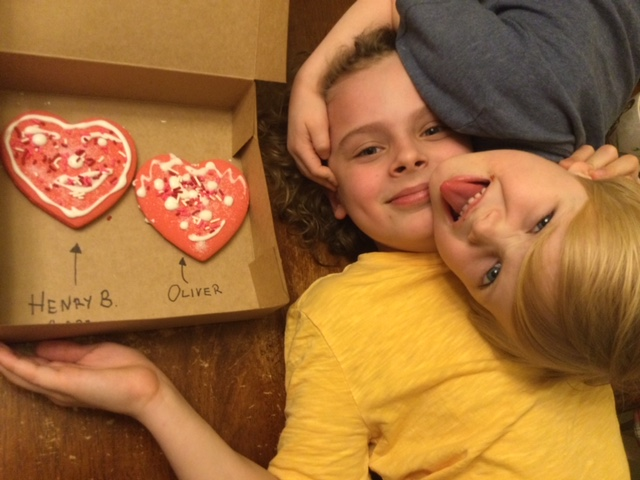 siblings showing their decorated heart cookies