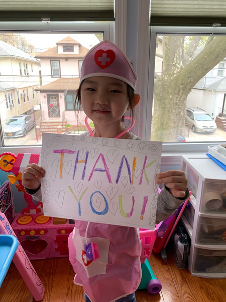 child holds a sign that says thank you
