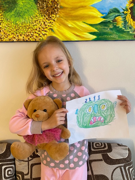 girl holds her monster and a teddy bear