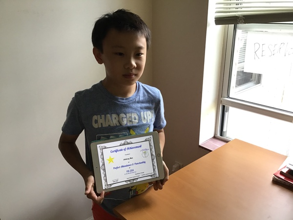 child holds certificate on an iPad near a window