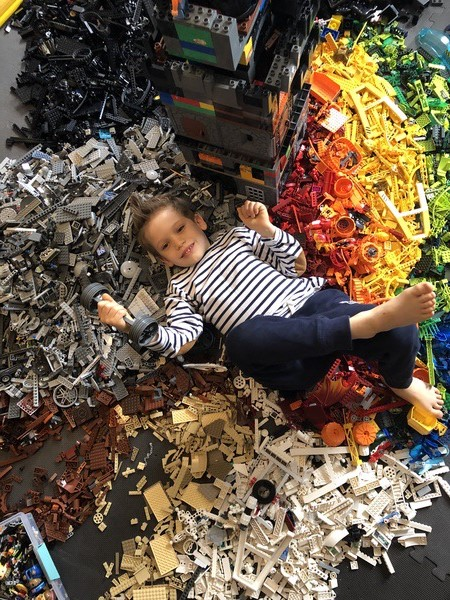 boy lays surrounded by legos