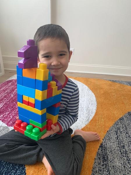 Smiling boy shares his Lego building