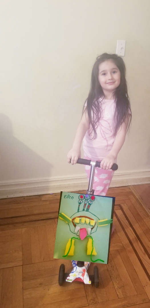 child on scooter with monster drawing on the floor