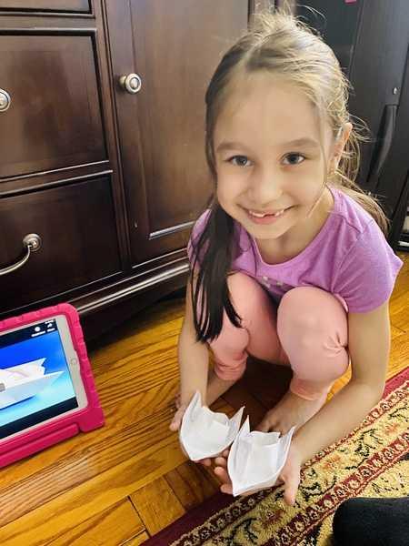 girl crouches down near iPad