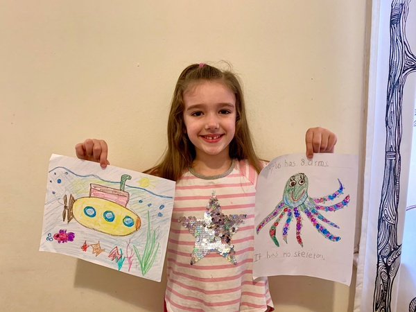 girl holds two of her drawings