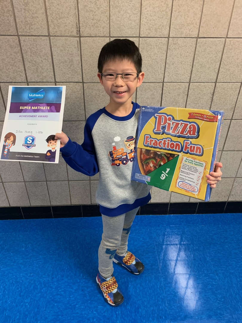 A first grade student holds his certificate and prize for Mathletics!