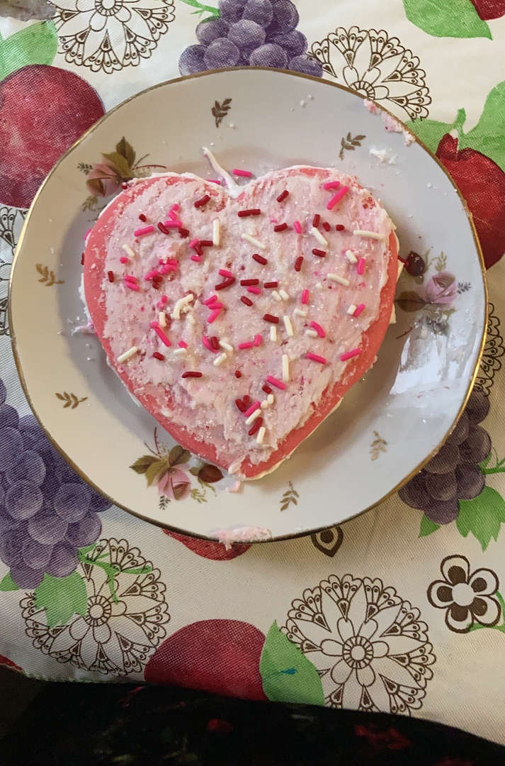 a pink decorated heart cookie with sprinkles