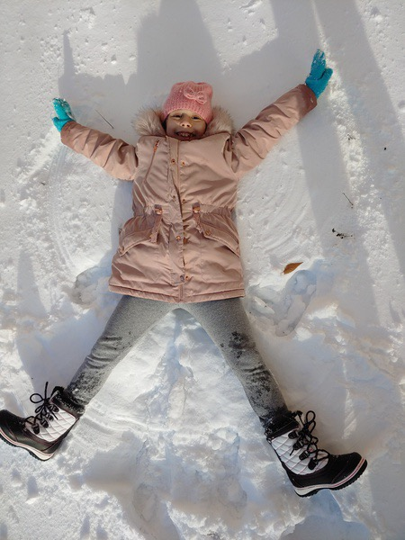 girl making a snow angel in the snow