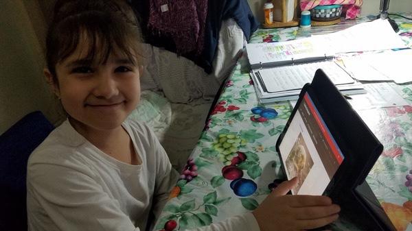 Girl smiles during a virtual trip to the aquarium