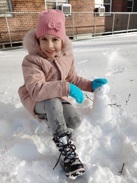 girl building a small snowman in a pink coat