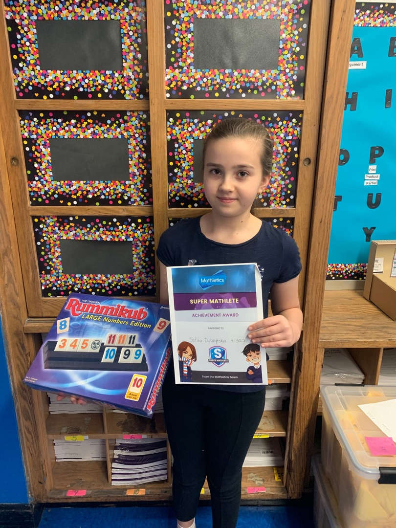A student stands in her classroom and holds a mathletics certificate and game.