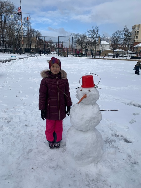 girl standing next to a snowman with a red hat and a carrot nose