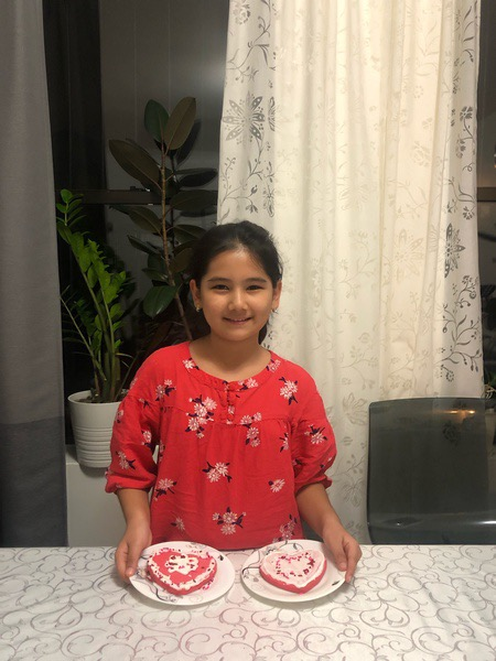 girl in red shirt showing her decorated cookies
