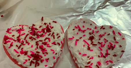 2 cookies with frosting and sprinkles on tin foil