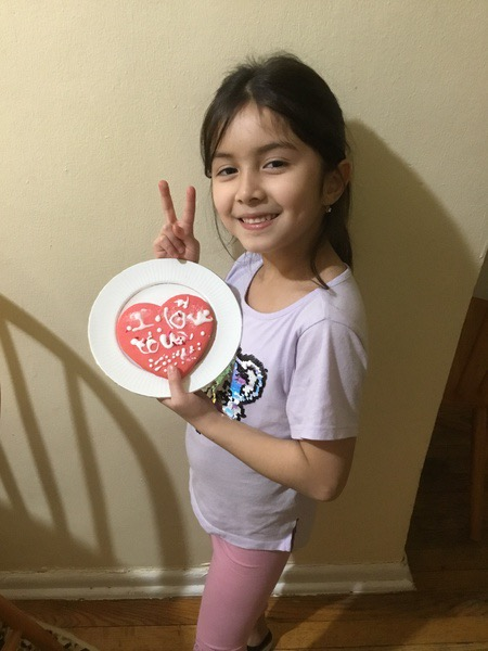 student showing her decorated heart with two fingers up
