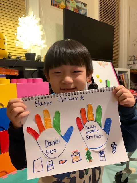 boy holding his family project with colorful fingers