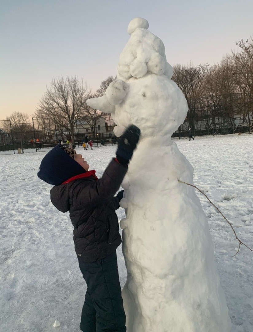 a boy building a snowman taller than him