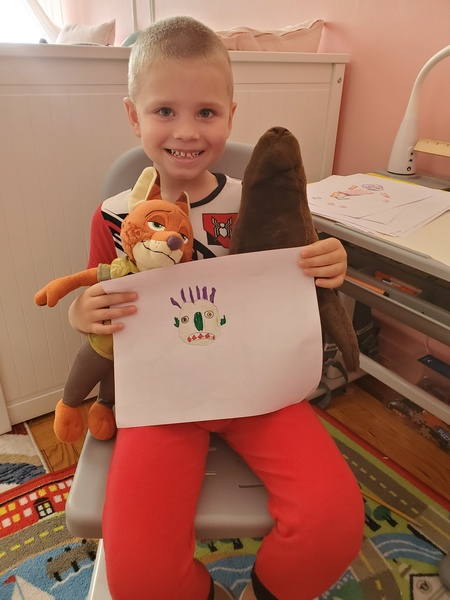 """<img src=""""drawing.png"""" alt=""""child standing holding drawing and stuffed animal"""">"""