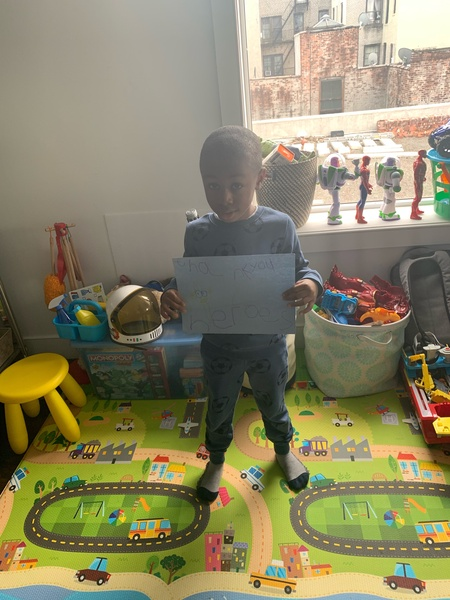 child holds his work in his play room