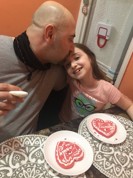 father and daughter decorating heart cookies