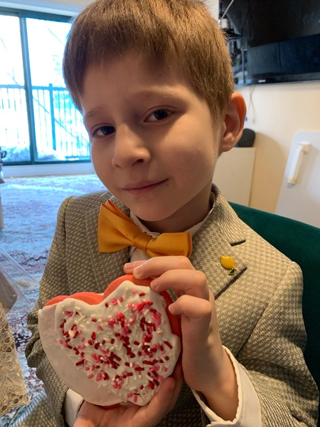 boy in yellow tie shows his decorated cookie