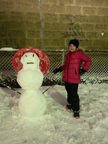 child in red coat with a snowman wearing a hat