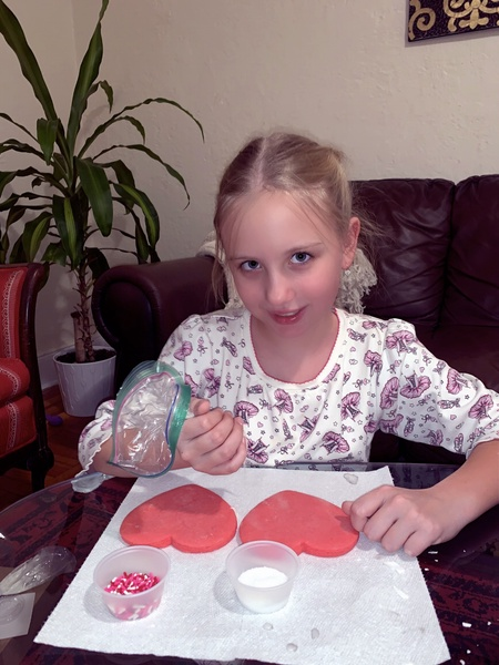 student decorating her pink heart cookie carefully