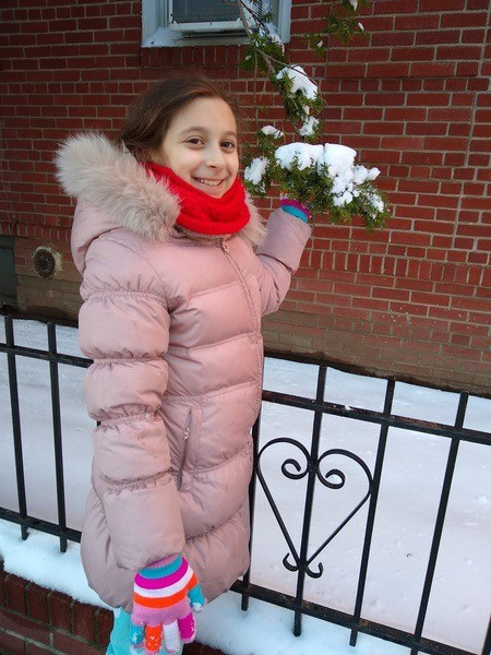 girl in pink coat with a handful of snow