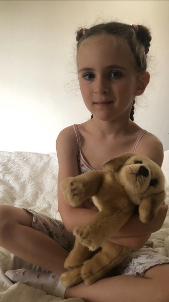 child standing holding a stuffed puppy