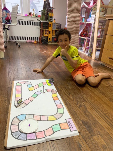 child gives a thumbs up next to the large board game he made