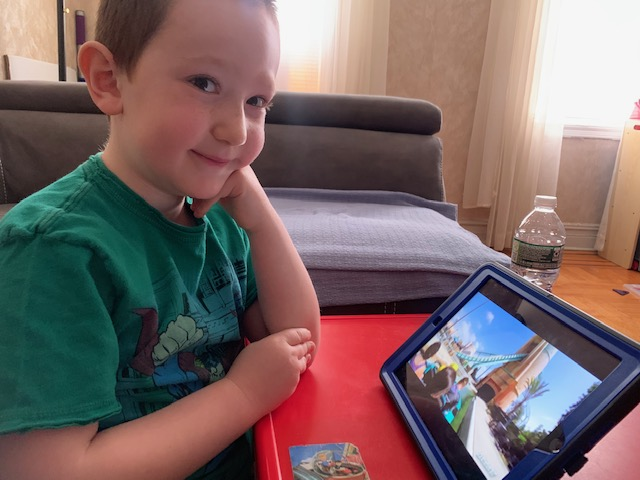 child sits at the the red table with the iPad