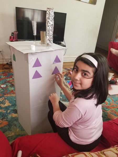 the girl places triangles on the box