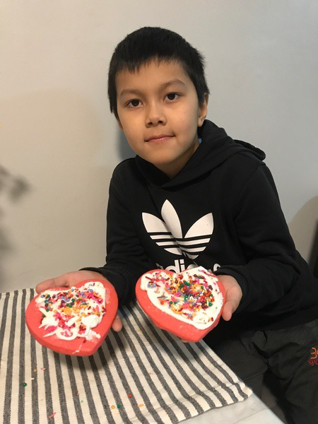 child shows two heart decorated cookies