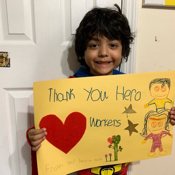 a boy holds a sign that says thank you hero workers