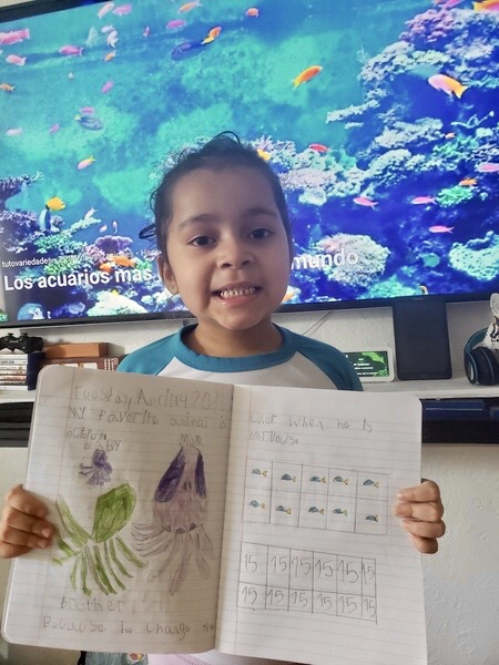 child shares their work in front of fish