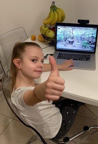 the girl gives a thumbs up near the computer screen